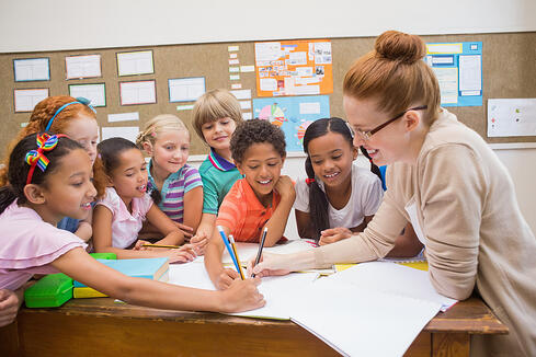 Teacher and pupils working at desk together at the elementary school-1